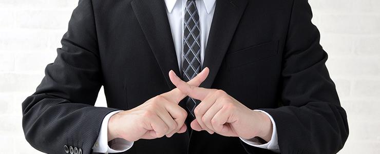 指でバツを作るサラリーマン
